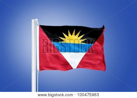 Flag of Antigua and Barbuda flying against a blue sky.