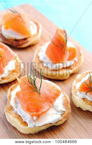 Appetising smoked salmon and cream cheese blinis on a wooden platter