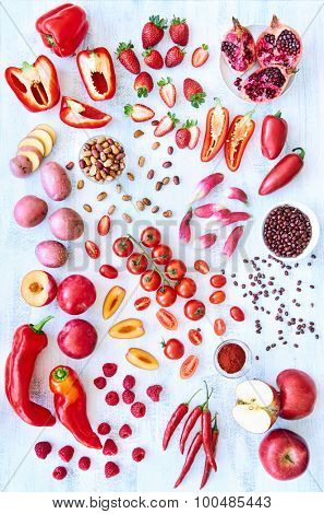 Collection of fresh red toned vegetables and fruits raw produce on white rustic background, peppers capsicum chilli strawberry raspberry pomegranate tomato paprika azuki beans plum poster