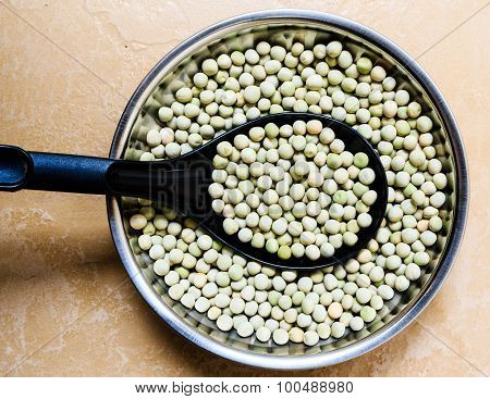 Dried green peas kept on a bowl on a plain background