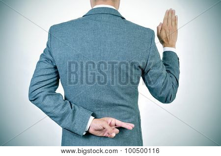 a young man in suit swearing an oath, rising his right hand, crosses his fingers in his back
