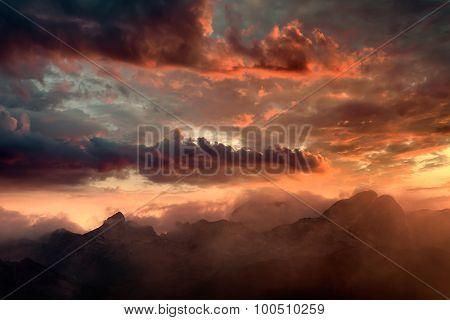 Fiery Sunset And Hazy Mountain Peaks