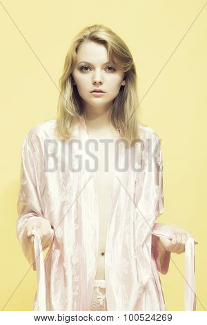 One young sexual concentrated blonde woman in satin pink dressing gown in soft flower pattern pastel colour pulling belt with hands standing on yellow studio background vertical picture poster