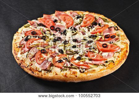 hot tasty delicious rustic homemade american pizza with tomato gherkin salami olives with thick crust on black table poster