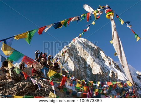 Tourists With Prayer Flags On View Point Kala Patthar