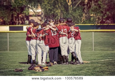 Baseball team in a huddle before a game.  Instagram toned image.