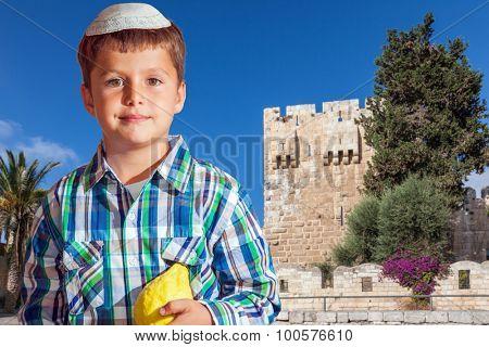 Sukkot in Jerusalem. Charming seven year old boy in white festive skullcap with etrog