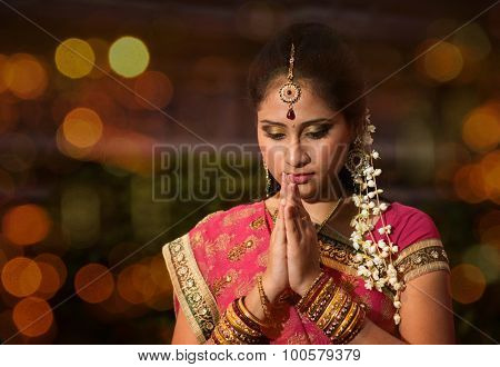 Indian female in traditional sari praying and celebrating Diwali or deepavali, fesitval of lights at temple. Girl prayer hands folded, beautiful lights bokeh background.