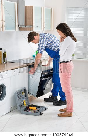 Young Woman Looking At Male Worker In Overall Repairing Oven In Kitchen poster