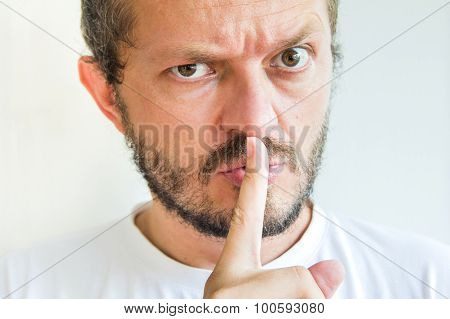 Bearded man making silence gesture