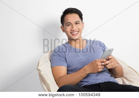 Man Holding A Handphone While Sitting On The Chair