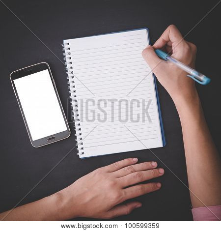 Hand Holding A Pen, With A Notes And Handphone, Black Background