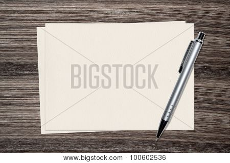 Sliver Pen and paper on wood background