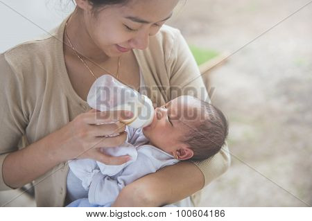 Cute Newborn Baby Being Fed By Her Mother Using Bottle