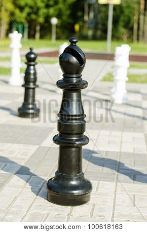 Chessman black bishop is in the street on the stone chessboard