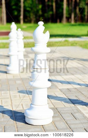 Chessman white bishop is in the street on the stone chessboard
