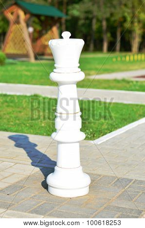 Chessman white king is in the street on the stone chessboard