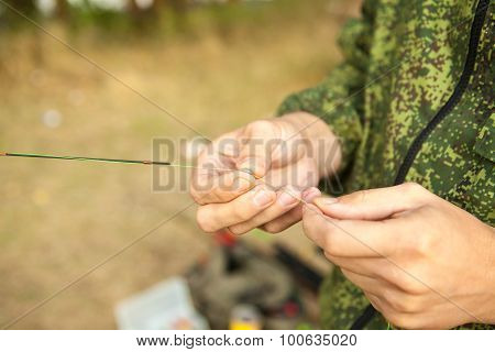 The Fisherman Attaches A Sinker On The Line