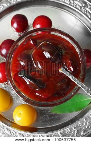 Tasty homemade plum jam in lass saucer on metal tray, closeup
