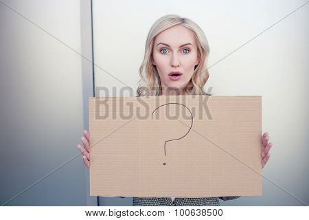 Attractive woman is presenting a placard with interrogation point