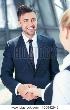 Attractive man in suit receives handshake from his colleague