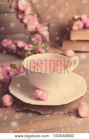 Cup of tea and beautiful fruit blossom on table