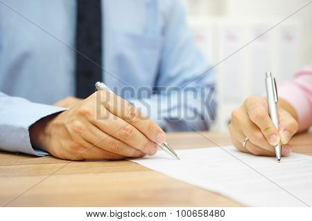 Businessman And Woman Hand Signing Agreement In Office