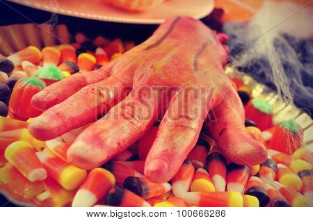 closeup of a scary amputated hand on a tray with some different Halloween candies and cobwebs, with a filter effect
