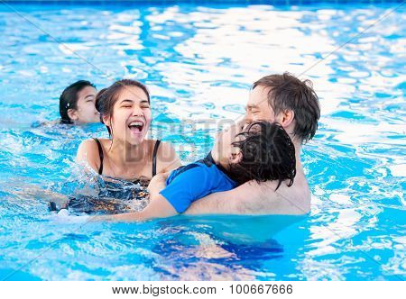 Multiracial Family Swimming Together In Pool. Disabled Youngest Son.