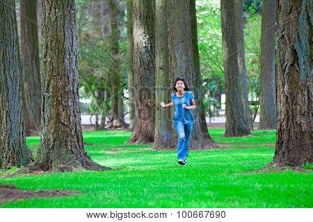 Young Teen Biracial Girl Walking Under Tall Trees