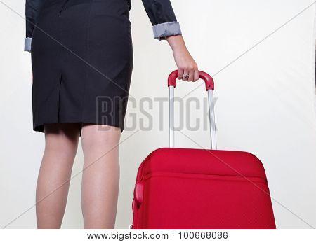 a businesswoman with a red suitcase as hand luggage