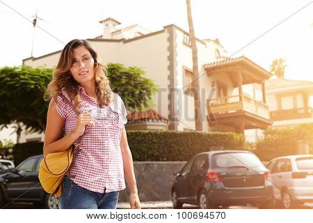 Caucasian Woman Walking Down The Street At Sunset