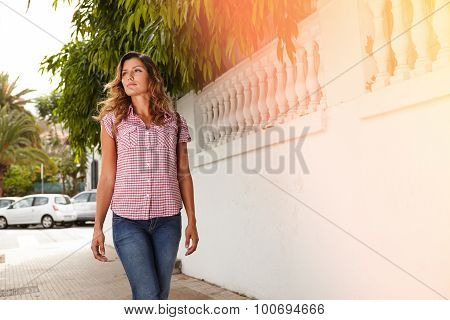 Young Woman Looking Away While Walking Outdoors