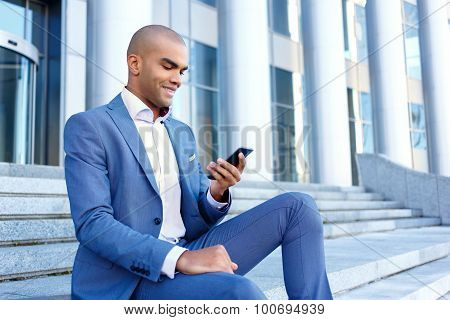 Nice businessman sitting on stairs