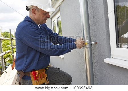 Workman Replacing Guttering On Exterior Of House poster
