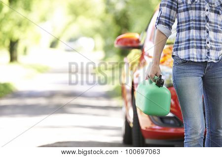 Female Motorist Carrying Fuel Can Next To Broken Down Car