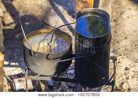 Background Two pot with water heated on the fire during a camping trip
