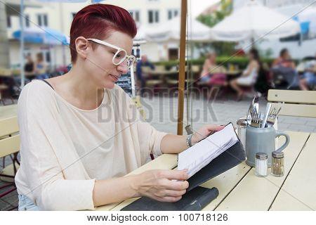 Woman At Restaurant Looking At Menu