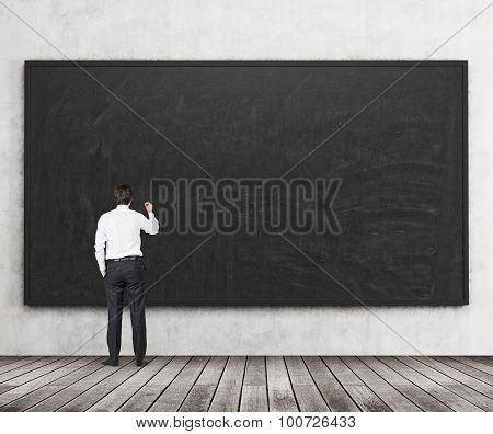 Rear View Of The Man Who Is Going To Write Something On The Black Chalkboard. Wooden Floor And Concr