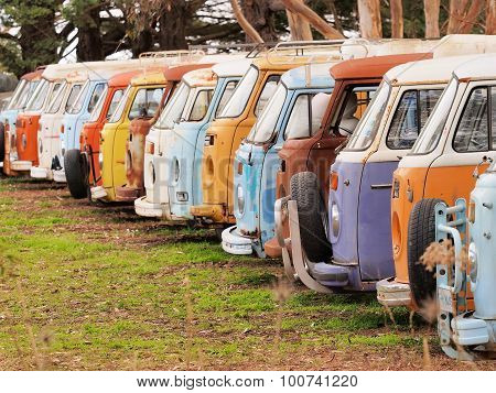 Row of defunct colorful and run down desolate vans of all the same Volkswagen Bully type