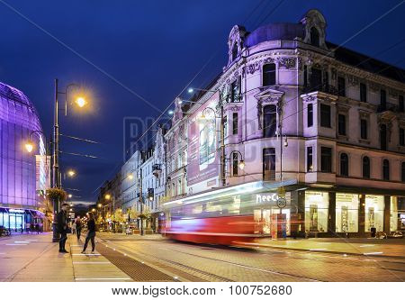 Street In The Center Of Katowice, Poland. The Old And The New Building, The Tram In Motion At Night.