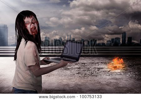 Creepy female zombie typing with laptop with city on fire background poster