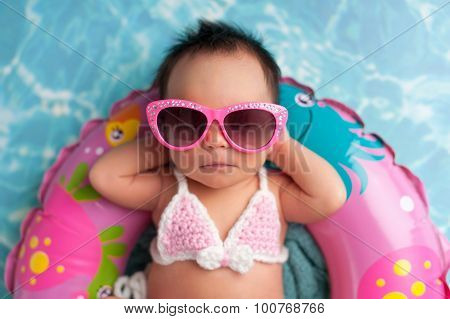 Newborn Baby Girl Wearing Sunglasses And A Bikini Top