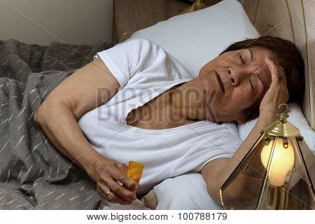 Senior Woman Preparing To Take Medicine At Nighttime Due To Insomnia