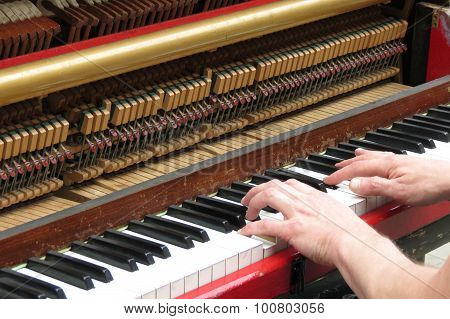 two hands playing an upright piano close up