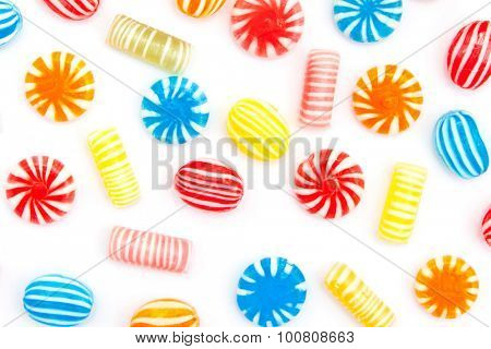 many different color candies on white
