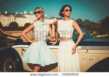 Two stylish ladies near classic convertible