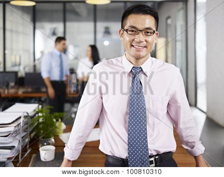 Asian Businessman Standing In Office Arms Crossed With Multinational Colleagues Talking In Backgroun