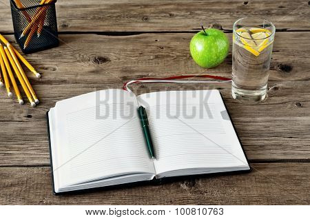 On The Desktop, Open Diary With Blank Pages And Office Accessories, Glass Of Water With Lemon And Ap