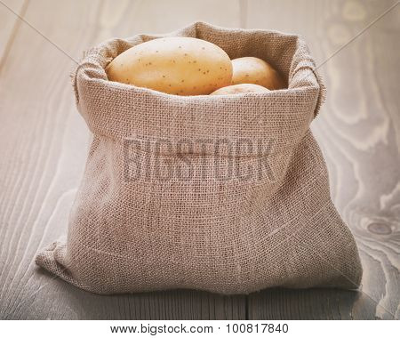organic raw potato in sack bag on wood table